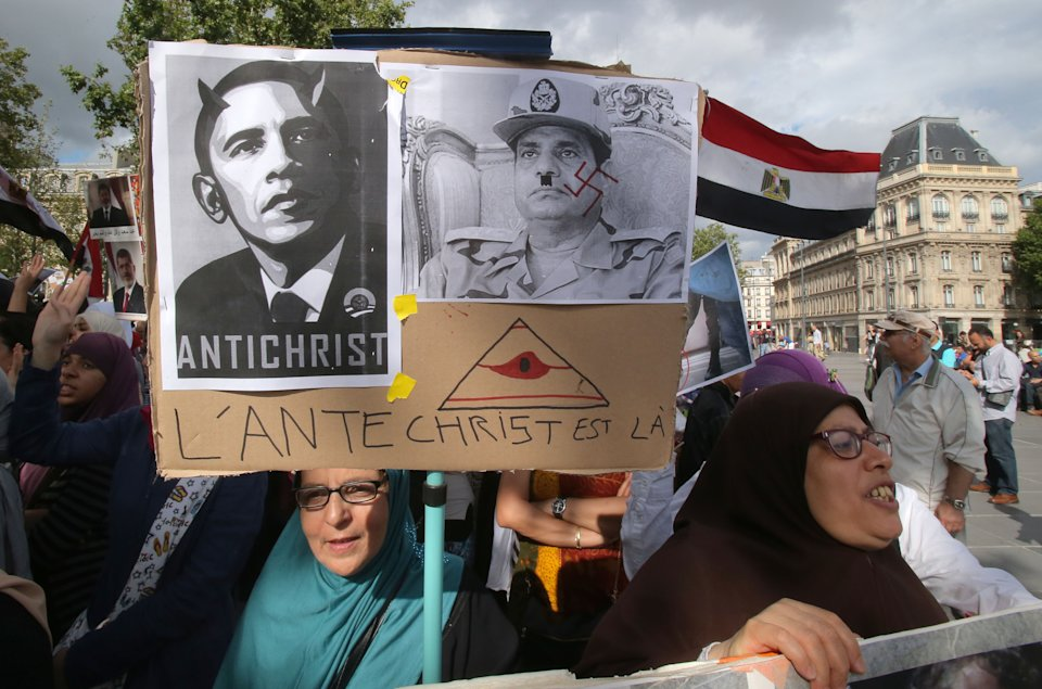 "Egyptian supporters of ousted Egyptian President Mohammed Morsi living in France, protest in Paris, Sunday, Aug. 18, 2013. Placard shows a pictures of American President with devil horns and Egyptian Defense Minister General Abdul Fatah al-Sisi as Adolf Hitler, which reads,""the anti Christ is here"". (AP Photo/Michel Euler)"