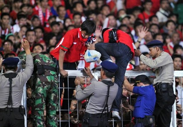 Indonesian security officials help evacuate supporters over a fence during the final match between Indonesian and Malaysia at the SEA Games.