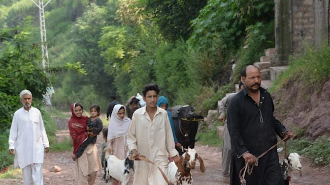 A Pakistani Kashmiri family flee from their house along with their livestock, following cross-border shelling, in Nakyal Sector, on the heavily militarised Line of Control (LoC), on August 18, 2015