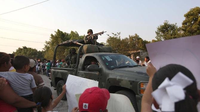 Mexican army soldiers enter the town of La Ruana, Michoacan, Mexico, Monday, May 20, 2013. Residents of western Mexico towns who endured months besieged by a drug cartel are cheering the arrival of hundreds of Mexican army troops. Hundreds of people in the state of Michoacan have taken up arms to defend their villages against drug gangs, a vigilante movement born of frustration at extortion, killings and kidnappings in a region wracked by violence. (AP Photo/Marco Ugarte)