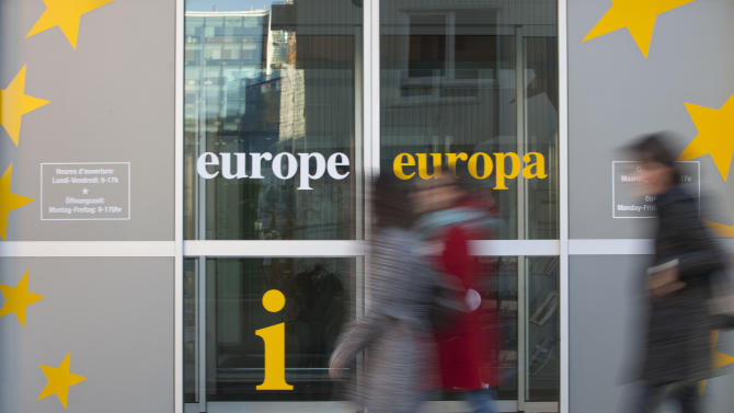 People walk in front of an information office outside of an EU summit in Brussels on Thursday, Nov. 22, 2012. Leaders from around Europe are arriving in Brussels Thursday for what promises to be a turbulent summit on the budget for the 27-country European Union. And for once, Britain will be at the heart of the debate. (AP Photo/Virginia Mayo)