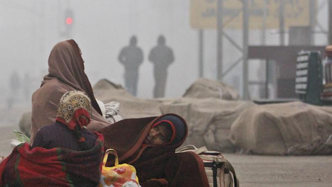 Passengers wait for a train amidst morning fog in Jammu, India, Friday, 26, 2014. Cold wave conditions continue unabated in the northern region with fog enveloping most areas and affecting transport services. (AP Photo/Channi Anand)