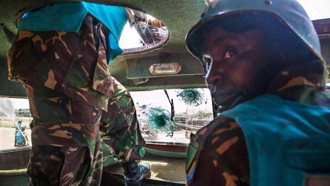 """In this Sunday, July 14, 2013 photo made available by the United Nations African Union Mission in Darfur , UNAMID military personnel from Tanzania, drive inside their base, in one of the Armored Personnel Carrier (APC) that was visible damaged after being ambushed Saturday, in Khor Abeche, South Darfur, Sudan. The killing of seven Tanzanian peacekeepers in Sudan's western region of Darfur is """"shocking to Tanzania, """" the country's deputy foreign minister said Sunday, July 14, 2013. Tanzanian officials do not yet have full details of the ambush Saturday in which 17 others were also wounded in the deadliest single attack on international peacekeepers in Sudan, said Mahadhi Juma Maalim on Sunday. (AP Photo/UNAMID, Albert González Farran)"""