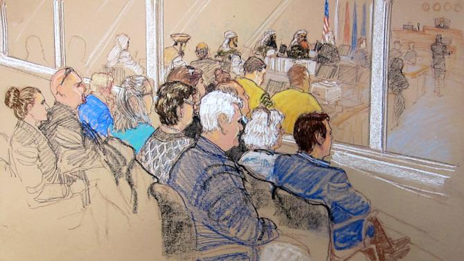 In this pool photo of a sketch by courtroom artist Janet Hamlin and reviewed by the U.S. Department of Defense, the relatives of Sept. 11 attacks victims, and staff members of the Office of Military Commissions (OMC), watch from behind a glass window a hearing on pretrial motions for the death penalty case against Sept. 11 defendants at the Guantanamo Bay U.S. Naval Base in Cuba, Monday, Jan. 28, 2013. They are, OMC's Patricia Moss, left, OMC's Domini McDonald, second left. Center row from left, Debra Strickland, Phyllis Rodrigues, Joyce Woods and John Woods. Front row from left, Loreen Sellitto, Matt Sellitto, Anne Gabriel and Christopher Gabriel. (AP Photo/Janet Hamlin, Pool)