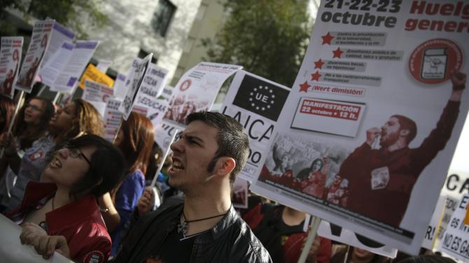 Demonstrators hold banners and shout slogans during protest on second day of a nationwide student strike against rising fees and educational cuts in Madrid