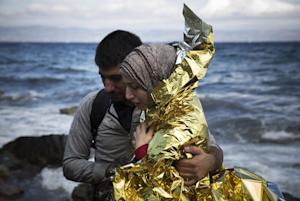 A Syrian couple hugs after its arrival on a dinghy…