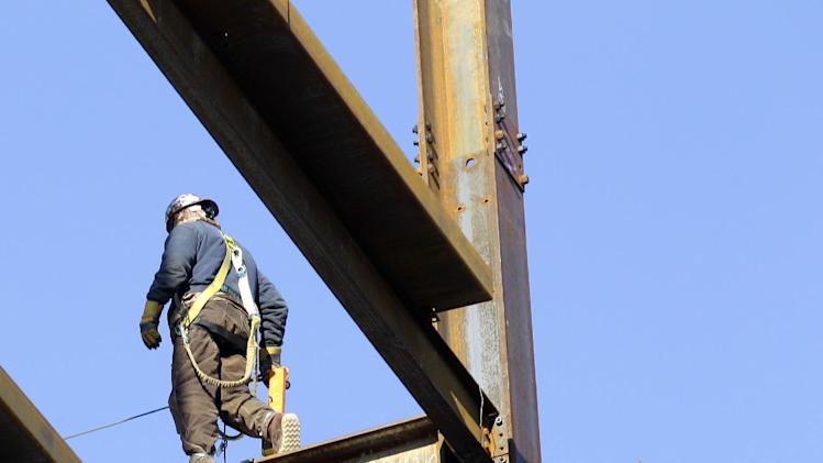 In this Feb. 9, 2012 photo, an iron worker walks atop an I-beam at a construction site in Cleveland. A sharp drop in commercial building projects caused a slight decline in construction spending in January. But the dip comes after previous figures were revised much higher. (AP Photo/Amy Sancetta)