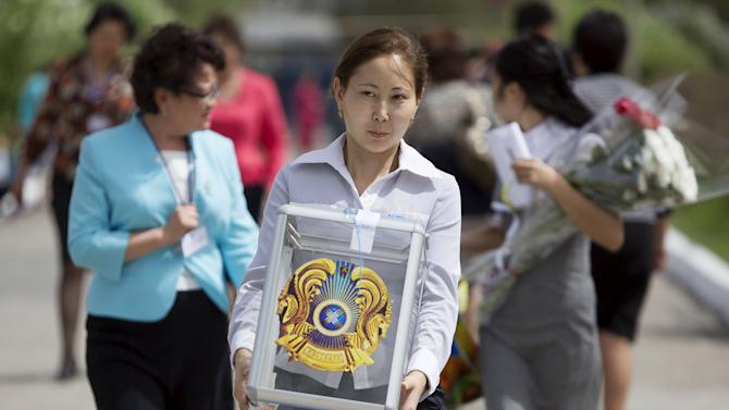 A member of a local election committee carries a ballot box during a snap presidential election in the village of Besagash, Kazakhstan