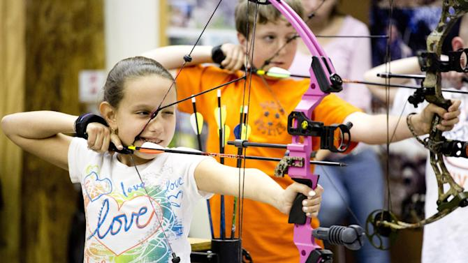 """In this April 13, 2012 photo, Ashley Donzella, of Fair Lawn, N.J., participates in the youth archery league at Targeteers Archery in Saddle Brook, N.J.  In schools and backyards, for their birthdays and out with their dads, kids are gaga for archery a month after the release of """"The Hunger Games."""" Archery ranges around the country have enjoyed a steady uptick among kids of both sexes in the movie's lead-up, though 16-year-old heroine Katniss Everdeen, the archery ace seems to resonate with girls more than boys. (AP Photo/Charles Sykes)"""