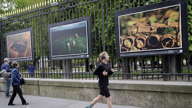 "A woman runs next to "" ""A rusting rifle"" a picture by British photographer Michael St Maur Sheil at the Paris Luxembourg gardens, Tuesday, April 8, 2014 as part of an exhibition "" Fields of Battle - Lands of Peace 14-18 "". Captured over a period of seven years, Michael's photography combines a passion for history and landscape and presents a unique reflection on the transformation of the battlefields of the Great War into the landscape of modern Europe. (AP Photo/Christophe Ena)"