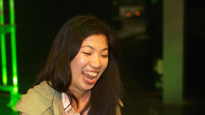 """IMAGE DISTRIBUTED FOR GROLSCH - Lily Han, from the Asia, demonstrates a novel way of opening a Grolsch beer bottle at the inaugural Grolsch Swingtop Open event  in Zaandam, Netherlands, on Friday, Oct. 12, 2012. The Dutch beer brand is known internationally for its iconic Swingtop bottle, first introduced in 1897. Over 30 contenders from around the world took part in Friday's event in front of a live audience and a panel of judges. Competitors have been practicing established moves like the """"Booty Pop"""", the """"Swing Top Chop"""" and """"The Drop"""" and honing innovative tricks in anticipation of the Swingtop Open. The eight finalists were challenged to pop open 30 bottles in the fastest time and the victor was crowned the Swingtop Open Master. (Mark van Wegen for Grolsch via AP Images)"""