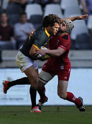 South African centre Jan Serfontein (L) is tackled…