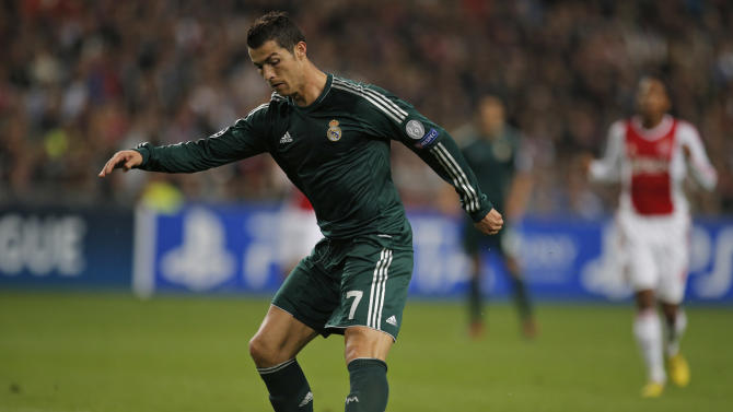 Real Madrid player Cristiano Ronaldo tips the ball over Ajax goalkeeper Kenneth Vermeer, not seen, to score 4-1 during the Champions League Group D soccer match at ArenA stadium in Amsterdam, Netherlands, Wednesday Oct. 3, 2012. (AP Photo/Peter Dejong)