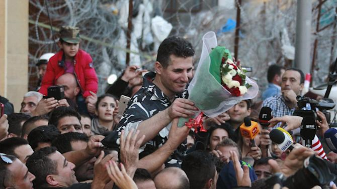 A newly released policeman, who was captured by the al Qaeda-linked Nusra Front in Arsal, is welcomed by his relatives during a celebration outside the government palace in downtown Beirut