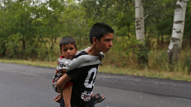 Children of Afghan migrants walk down a road after crossing the border illegally from Serbia, near Asotthalom