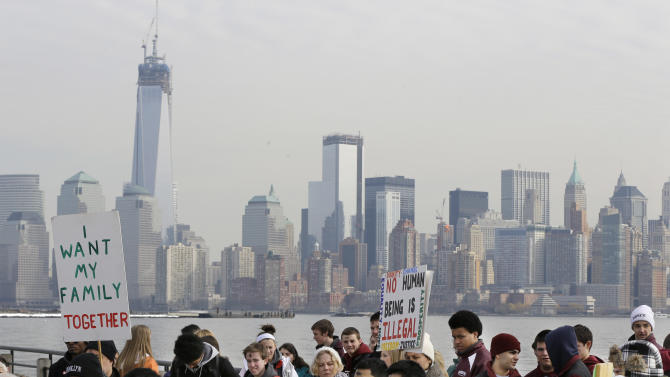 FILE - In this Feb. 13, 2013, file photo, before the New York skyline, a group of immigrant rights advocates gather near Ellis Island in Liberty State Park, Jersey City, N.J. A dispute between business and labor groups over wages for low-skilled workers is a final issue holding up a deal on a sweeping immigration bill in the Senate on Friday, March 22, 2013. (AP Photo/Mel Evans, file)