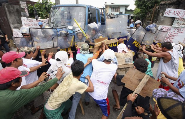 Laid-off workers from local steel manufacturing company clash with anti-riot police during a picket rally to demand their jobs back, in Quezon City