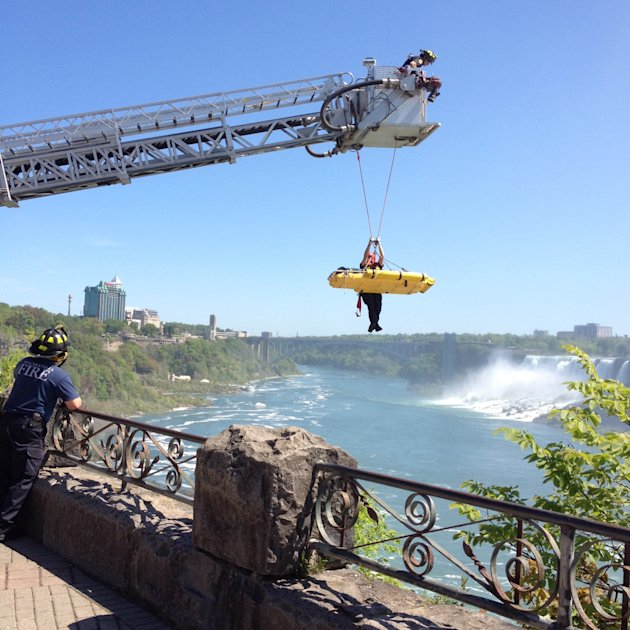 In this photo provided by Jared Fisk, Niagara Falls emergency officials rescue a man who plunged over Niagara Falls and survived in an apparent suicide attempt, Monday, May 21, 2012. The man is only t
