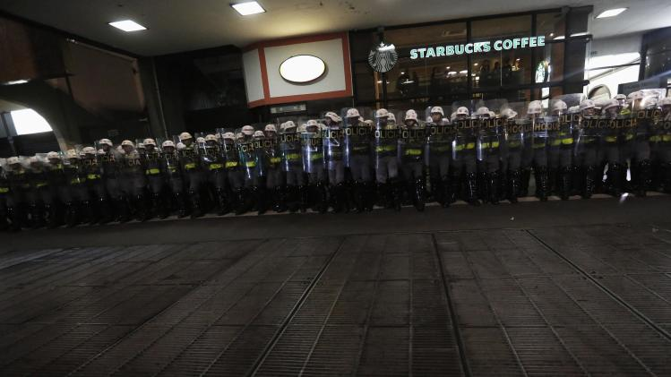 Military police stand guard in front of a Starbucks coffee shop during a protest against the 2014 World Cup, in Sao Paulo