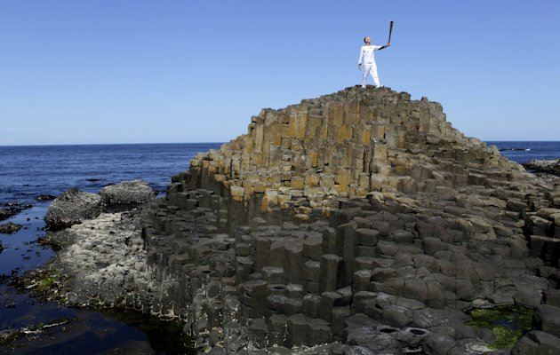 Peter Jack holds the Olympic torch aloft at the Giant's Causeway in county Antrim, Northern Ireland, Monday, June 4, 2012.   The Olympic Torch is continuing its relay journey around the country, and i