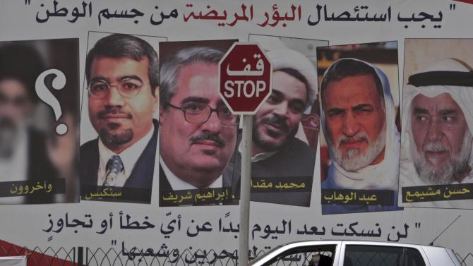 """A car passes a pro-government billboard Sunday, May 8, 2011, in Muharraq, Bahrain, with pictures of jailed Bahraini Shiite and Sunni opposition leaders with their names written below, right to left: Hassan Meshaima, Abdel Wahab Hussein, Mohamed Muqdad, Ibrahim Sharif, Abdel Jalil Singace and a question mark over a blurred picture depicting a Shiite cleric that reads beneath it """"And others."""" At top, the sign reads: """"Disease must be excised from the body of the nation,"""" and at bottom: """"We won't keep quiet after today about any mistakes or excesses by those whom abuse Bahrain and its people."""" Bahrain's military prosecutor accused 21 political activists Sunday, including those on the billboard, of seeking to overthrow the ruling monarchy with the help of a foreign terrorist group, an apparent reference to Iranian-backed militants in a widening crackdown on a pro-reform uprising led by the island nation's Shiite majority. (AP Photo/Hasan Jamali)"""