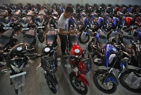A worker cleans a Bajaj motorcycle at a Bajaj showroom in Kolkata October 16, 2013. REUTERS/Rupak De Chowdhuri