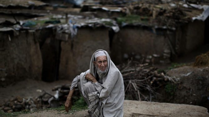 Pakistani Wazeer Khan, 87, sits on a roadside near his home, on the outskirts of Islamabad, Pakistan, Monday, April 1, 2013. Khan and his family fled Pakistan's tribal area of Bajur in 2009, due to fighting between the Taliban and the army, and took refuge in Islamabad. (AP Photo/Muhammed Muheisen)