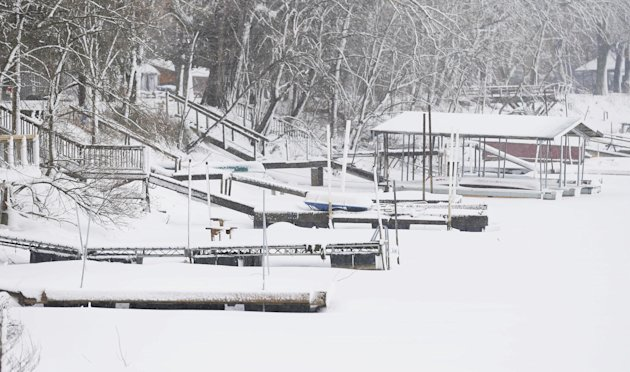 Snow covers docks the no longer reach the low water of Lakeview, a private lake and club, near Lawrence, Kan., Tuesday, Feb. 26, 2013. For the second time in a week, a major winter storm paralyzed parts of the nation's midsection Tuesday, dumping a fresh layer of heavy, wet snow atop cities still choked with piles from the previous system and making travel perilous from the Oklahoma panhandle to the Great Lakes. The weight of the snow strained power lines and cut electricity to more than 100,000 homes and businesses. At least three deaths were blamed on the blizzard. (AP Photo/Orlin Wagner)