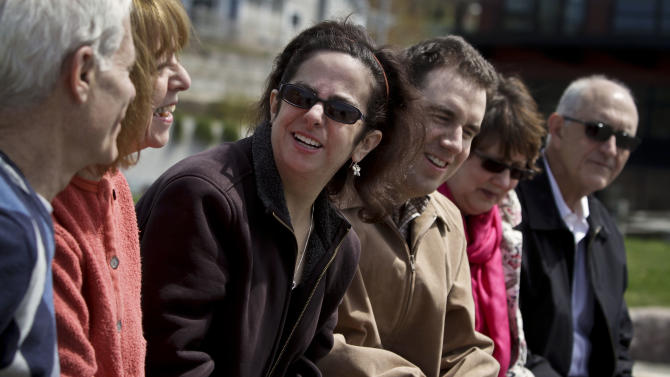 Hava Samuels, third from left, and her husband Paul Farziano, third from right, sit with their parents Norman Samuels, far left and Bonnie Samuels, second from left, and Frank Farziano, far right, and Rosann Farziano, second from right,  during an interview on Thursday, April 25, 2013 in Port Jefferson, N.Y.   Paul and Have, a developmentally disabled couple, has brought a lawsuit against the group facilities where they live for violating the Disability Act, by refusing them residence as a married couple.  (AP Photo/Bebeto Matthews)