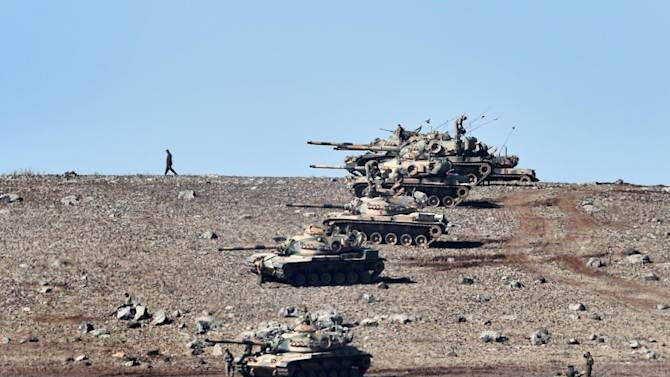 Turkish tanks line up on a hill outside the village of Mursitpinar next to the Syrian town of Ain al-Arab, known as Kobane by the Kurds, on the Turkish-Syrian border in the southeastern town of Suruc, Sanliurfa province, on October 6, 2014