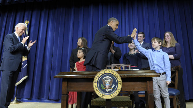 President Barack Obama, accompanied by Vice President Joe Biden, left, gets a high-five from eight-year-old letter writer Grant Fritz during a news conference on proposals to reduce gun violence, Wednesday, Jan. 16, 2013, in the South Court Auditorium at the White House in Washington. Obama and Biden were joined by law enforcement officials, lawmakers and children who wrote the president about gun violence following the shooting at an elementary school in Newtown, Conn., last month. (AP Photo/Susan Walsh)