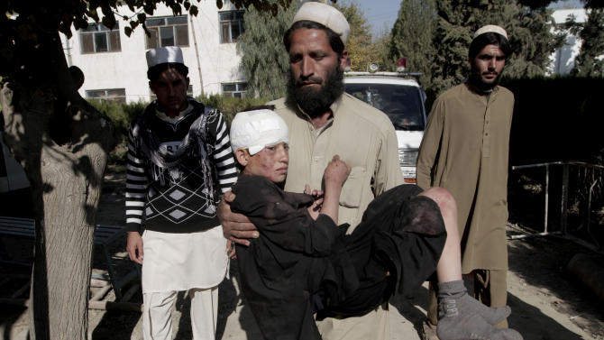 FILE - In this file photo taken Thursday, Nov. 28, 2013, an Afghan man carries an injured boy to a hospital after two roadside bombs struck the Achin district of Jalalabad, east of Kabul, Afghanistan. The number of children killed and wounded in Afghanistan's war jumped by 34 percent in 2013 as the Taliban intensified armed attacks across the country and continued to lay thousands of roadside bombs, according to a U.N. report Saturday, Feb. 8, 2014. (AP Photo/Rahmat Gul, File)