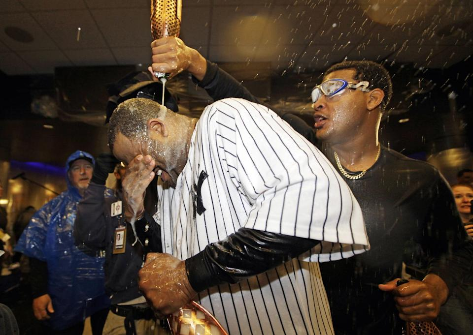 New York Yankees starting pitcher CC Sabathia is doused with champagne by teammate Ivan Nova, right, after Game 5 of the American League division baseball series against the Baltimore Orioles Friday, Oct. 12, 2012, in New York. The Yankees won the game 3-1 and advanced to the AL championship. (AP Photo/Kathy Willens)