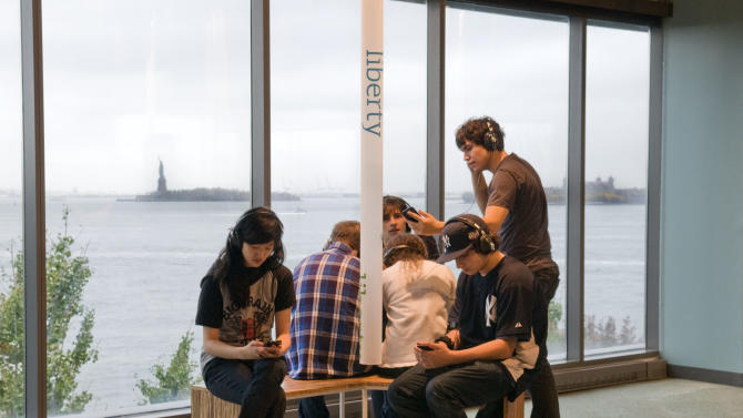 """In this 2009 photo released by the Museum of Jewish Heritage-A Living Memorial to the Holocaust, young visitors at the museum listen to a sound installation called """"Voices of Liberty,"""" in which Holocaust survivors, refugees and others discuss why they chose to make the U.S. their home. The museum is located in Lower Manhattan and offers a view of the Statue of Liberty through its picture windows, one of many different vantage points around the city for seeing the statue. (AP Photo/Museum of Jewish Heritage-A Living Memorial to the Holocaust, Melanie Einzig)"""