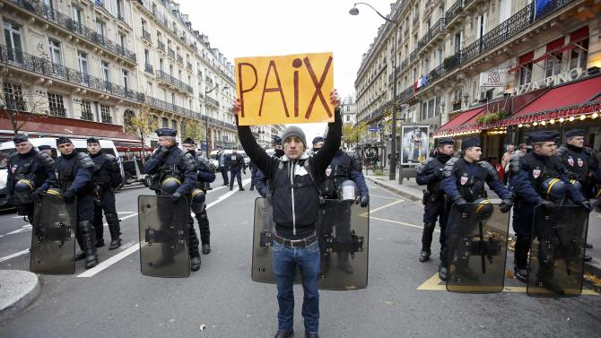 """A man holds a placard which reads """"Peace"""" in front of CRS riot policemen near the Place de la Republique ahead of the World Climate Change Conference 2015 in Paris"""
