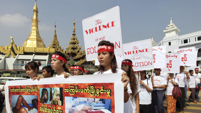 """Holding placards which read """"The violence is not solution,"""" activists march in protest against recent violence in central Myanmar, Monday, Dec. 10, 2012, in downtown Yangon, Myanmar. About 50 activists staged the protest to mark International Human Rights Day. (AP Photo/Khin Maung Win)"""