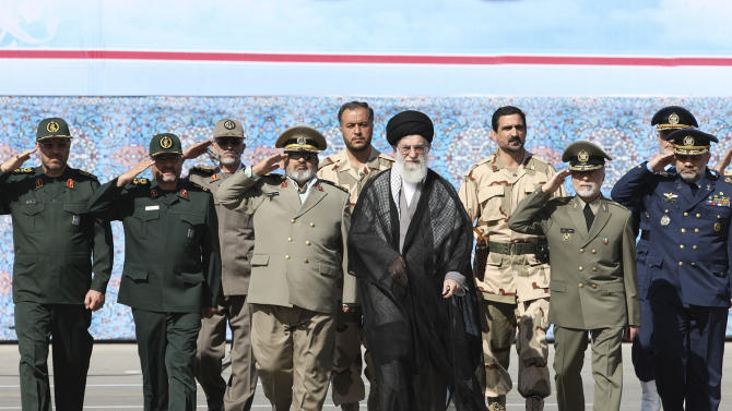 In this picture released by an official website of the office of the Iranian supreme leader, Supreme Leader Ayatollah Ali Khamenei, center, attends a graduation ceremony of army cadets accompanied by top military commanders, in Tehran, Iran, Saturday, Oct. 5, 2013. Iran's top leader hinted Saturday that he disapproved of the phone call between Presidents Hassan Rouhani and Barack Obama during the Iranian leader's trip to New York last month, but he reiterated his crucial support for the president's policy of outreach to the West. (AP Photo/Office of the Iranian Supreme Leader)