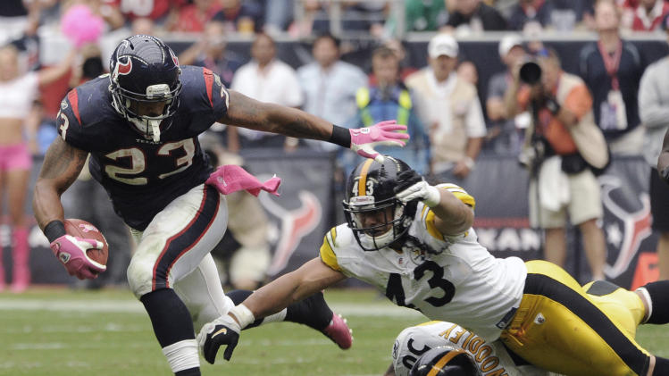 Houston Texans running back Arian Foster (23) breaks away from Pittsburgh Steelers' Troy Polamalu (43) and LaMarr Woodley (56) in the fourth quarter of an NFL football game Sunday, Oct. 2, 2011, in Houston. Foster went on to score a touchdown. (AP Photo/Dave Einsel)