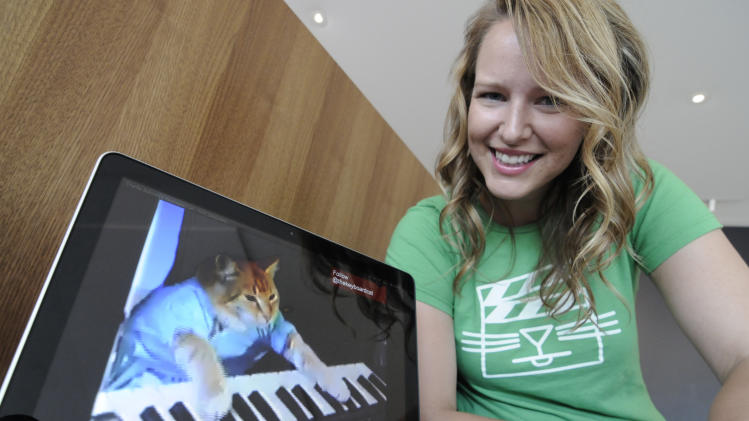 "Katie Hill, a program associate with the Walker Art Center, shows a frame from a cat video of a cat playing the piano Wednesday, Aug. 29, 2012, in Minneapolis. The Walker will present its  first ""Internet Cat Video Film Festival"" to showcase the best in filmed feline hijinks. (AP Photo/Jim Mone)"