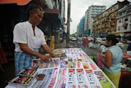 This file photo, taken in August, shows a vendor selling local magazines and newspapers on a road-side in Yangon. Myanmar was long a global outcast, but has been rapidly rehabilitated since polls that saw the election of a nominally civilian government