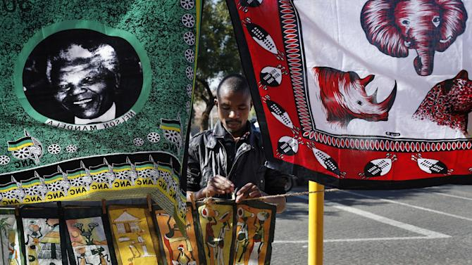 A souvenir merchant affixes batiks under a Mandela printed fabric in the Soweto township in Johannesburg, South Africa, Wednesday June 12, 2013.  Former South African president Nelson Mandela remained hospitalized for the fifth day with an occurring lung infection. The latest government report says that he remains in a serious but stable condition. (AP Photo/Jerome Delay)