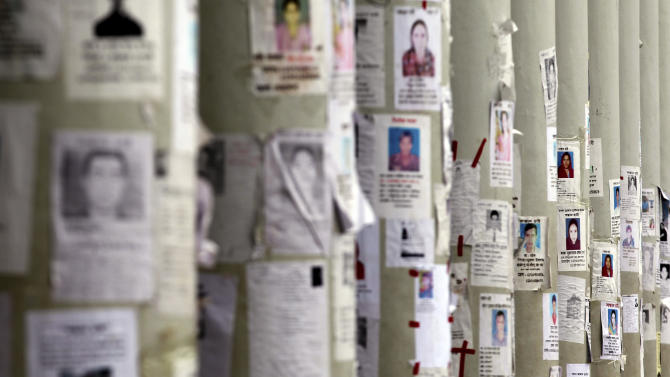 A school turned make-shift morgue has its walls plastered with portraits of missing persons, mostly workers at the garment factory building which collapsed, on Monday April 29, 2013 in in Savar, near Dhaka, Bangladesh. Rescue workers in Bangladesh gave up hopes of finding any more survivors in the remains of the building that collapsed five days ago, and began using heavy machinery on Monday to dislodge the rubble and look for bodies - mostly of workers in garment factories there. At least 381 people were killed when the illegally constructed, 8-story Rana Plaza collapsed in a heap on Wednesday morning along with thousands of workers in the five garment factories in the building.(AP Photo/Wong Maye-E)