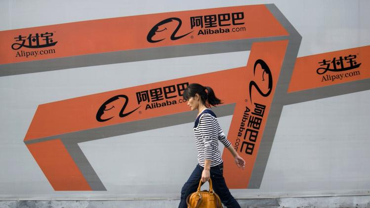 File picture shows a woman walking past an Alibaba advertisement on a wall in Hangzhou