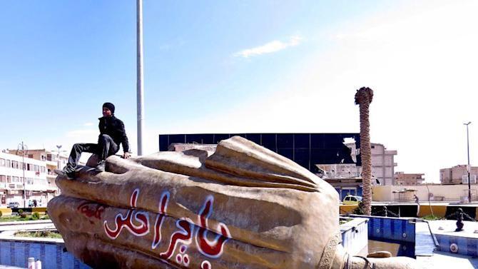 "FILE - In this Tuesday, March 5, 2013 file photo, citizen journalism image provided by Aleppo Media Center AMC which has been authenticated based on its contents and other AP reporting, shows Syrian man sitting on a fallen statue of former Syrian President Hafez Assad in a central square in Raqqa, Syria. The Arabic words on the fallen statue read: ""tomorrow will be better."" A quiet power struggle in taking place in the eastern city between Islamic extremist rebels, who control the city after capturing it four months ago from the regime, and moderates trying to curtail their influence, making it a test case for the opposition.(AP Photo/Aleppo Media Center AMC, File)"