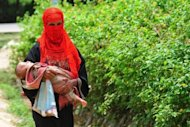 A Rohingya Muslim woman walks with her child at an unregistered refugee camp in Teknaf, Bangladesh in June 2012. Bangladesh has ordered three international charities to stop providing aid to Rohingya refugees who cross the border to flee persecution and violence in Myanmar, an official said Thursday