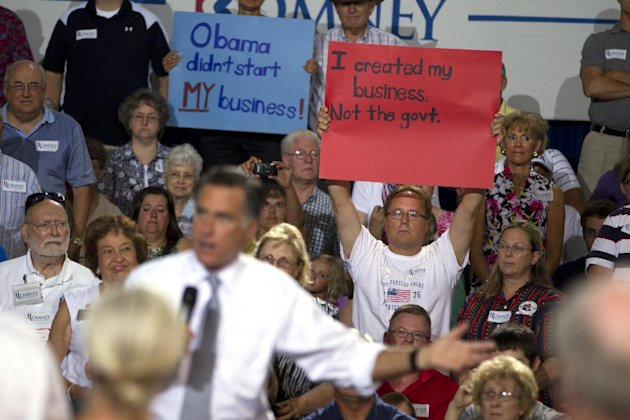 Supporters of Republican presidential candidate, former Massachusetts Gov. Mitt Romney hold up signs during a campaign stop on Wednesday, July 18, 2012 in Bowling Green, Ohio. (AP Photo/Evan Vucci)