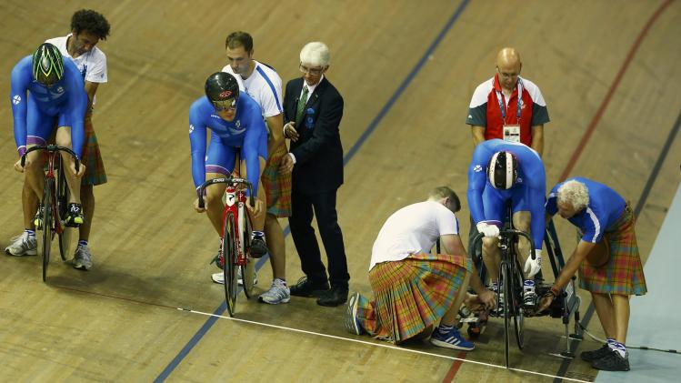 Scottish coaches assist Scotland's riders in the men's team sprint qualifying at the 2014 Commonwealth Games in Glasgow