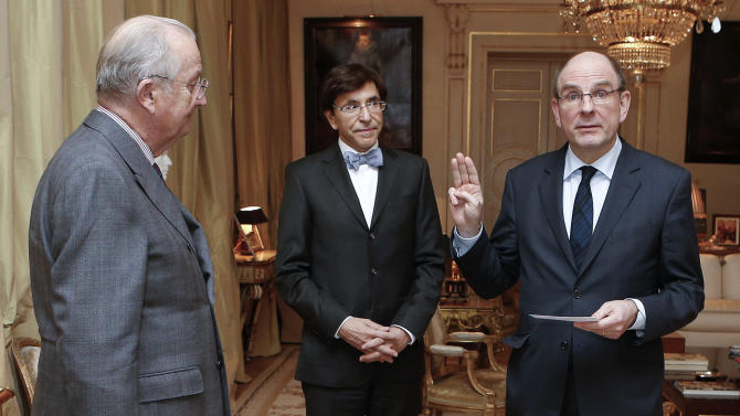 Belgium's newly appointed Minister of Finance Koen Geens, right, takes the oath of office in front of Belgium's King Albert II, left, and Belgium's Prime Minister Elio Di Rupo, center, at the Royal Palace in Brussels on Tuesday, March 5, 2013. Geens was appointed on Tuesday after Belgium's Minister of Finance Steven Vanackere resigned. (AP Photo/Bruno Fahy, Pool)