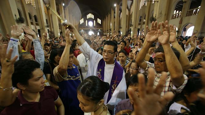 Filipino Catholic Priest Victorino Cueto, center, sprinkles holy water on devotees during a mass at the Shrine of Our Lady of Perpetual Help in suburban Paranaque, south of Manila, Philippines on Sunday Mar. 3, 2013. Filipinos in Asia's largest predominantly Roman Catholic nation on Sunday went to church that awkwardly had no pope for the first time in 600 years and prayed for the smooth rise of a successor to Benedict XVI who can lead an embattled church. (AP Photo/Aaron Favila)