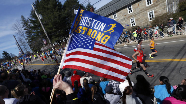 "A race fan waves the American flag and a banner bearing the slogan ""Boston Strong"" as runners compete in the 118th Boston Marathon Monday, April 21, 2014 in Hopkinton, Mass. (AP Photo/Michael Dwyer)"